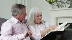 Mature Couple Sitting On Sofa And Looking At Photo Album. Together stock footage