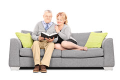 Mature couple sitting on sofa and reading a book Stock Photos