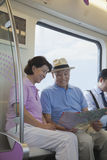Mature couple sitting in the subway and looking at the map Royalty Free Stock Image