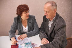 Mature couple sitting at a table. And decide money issues Royalty Free Stock Photography