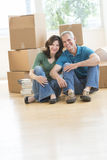 Mature Couple Sitting Together On Floor In New House. Portrait of mature couple sitting together on floor against cardboard boxes in new house Stock Photos