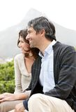 Mature couple sitting together and looking away Stock Photo