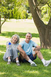 Mature couple sitting with water bottles at park Stock Images