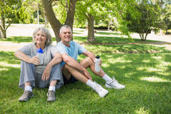 Mature couple sitting with water bottles at park Royalty Free Stock Images