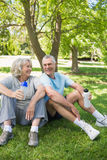 Mature couple sitting with water bottles at park Stock Photo
