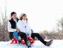 Mature couple sledding. Seniors couple on sled in winter park Royalty Free Stock Photography