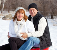 Mature couple sledding Royalty Free Stock Images