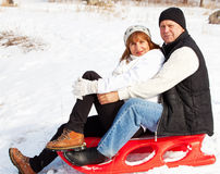 Mature couple sledding Royalty Free Stock Image