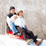 Mature couple sledding Royalty Free Stock Photography