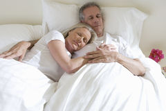 Mature couple sleeping in bed, woman leaning contentedly on man�s chest. Mature couple sleeping in bed, women leaning contentedly on man�s chest Royalty Free Stock Photography