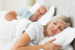 Mature couple sleeping with eyes closed in the bed. Closeup of a mature couple sleeping with eyes closed in the bed at home Royalty Free Stock Image
