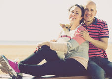 Mature couple with a small dog outdoors. Cheerful mature couple with a small dog smiling and holding each other at the beach Royalty Free Stock Image