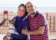 Mature couple with a small dog outdoors. Mature happy couple with a small dog smiling and holding each other at seaside Royalty Free Stock Photography