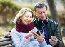 Mature couple with smartphones outdoors Stock Photos