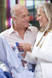 Mature couple smiling at each other in clothing store Stock Photo