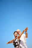 Mature couple smiling and embracing. Bright lifestyle portrait of a mature couple smiling and embracing over a blue sky background Stock Image
