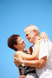 Mature couple smiling and embracing. Bright lifestyle portrait of a mature couple smiling and embracing over a blue sky background Royalty Free Stock Photography
