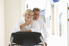 Mature couple smiling by running machine, woman holding glass of water Stock Photo