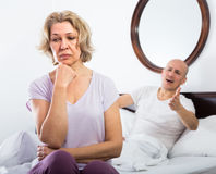 Mature couple sorting out relationships in bed Stock Images