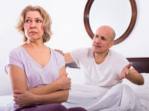 Mature couple sorting out relationships in bed Royalty Free Stock Photos