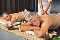 Mature couple in spa getting massage. Mature couple in spa salon getting body massage and looking at camera. Senior men and beautiful women relaxing at wellness stock images
