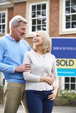 Mature Couple Standing Outside New Home With Sold Sign stock images