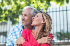 Mature couple standing against fence. Romantic mature couple standing against fence in city Royalty Free Stock Image