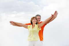 Mature couple standing with arms outstretched. Royalty Free Stock Images