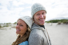 Mature couple standing back to back. On beach Royalty Free Stock Photos