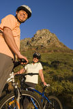 Mature couple standing with bicycles on mountain trail, smiling, low angle view, portrait Royalty Free Stock Image