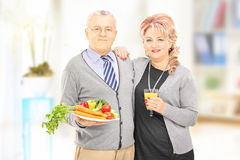 Mature couple standing close together holding a healthy food and Royalty Free Stock Photo