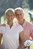 Mature couple standing on golf course, man with hand on woman�s shoulder, smiling, front view, portrait royalty free stock image