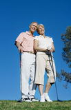 Mature couple standing on golf course, playing golf, man with arm around woman, smiling, portrait (surface level) Stock Photography