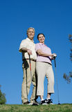 Mature couple standing on golf course, playing golf, man with arm around woman, smiling, portrait (surface level) Stock Image