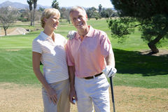 Mature couple standing on golf course, playing golf, woman leaning on man�s shoulder, smiling, portrait Stock Images