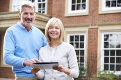 Mature Couple Standing Outside House Looking At Property Details stock photos