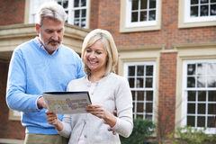 Mature Couple Standing Outside House Looking At Property Details Stock Photography