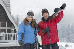 Mature Couple Standing Together In Snowing Weather. Portrait of happy mature couple standing together with skis and poles in snowing weather Royalty Free Stock Photos