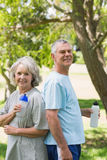 Mature couple standing with water bottles at park Stock Photography