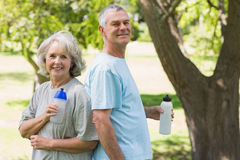 Mature couple standing with water bottles at park Stock Image