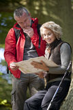 A mature couple standing in woodland looking at a map, close up Royalty Free Stock Photo