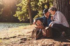 Mature couple stops to check their position while hiking. Mature couple stops to check their position by using a compass while out on hike in the forest. Man and Stock Image