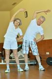 Mature couple stretching in gym Royalty Free Stock Photography