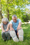 Mature couple stretching hands to legs at park Royalty Free Stock Photo