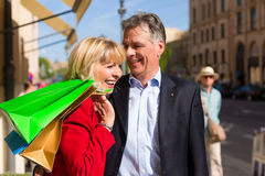 Mature couple strolling through city shopping Royalty Free Stock Photo