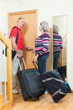 Mature couple with suitcases near door Stock Photo