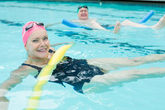 Mature couple swimming with pool noodles Stock Photography