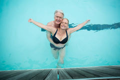Mature couple swimming in pool Stock Image