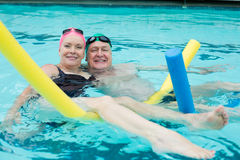 Mature couple swimming in pool Stock Images