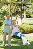 Mature couple at swing in park Royalty Free Stock Images